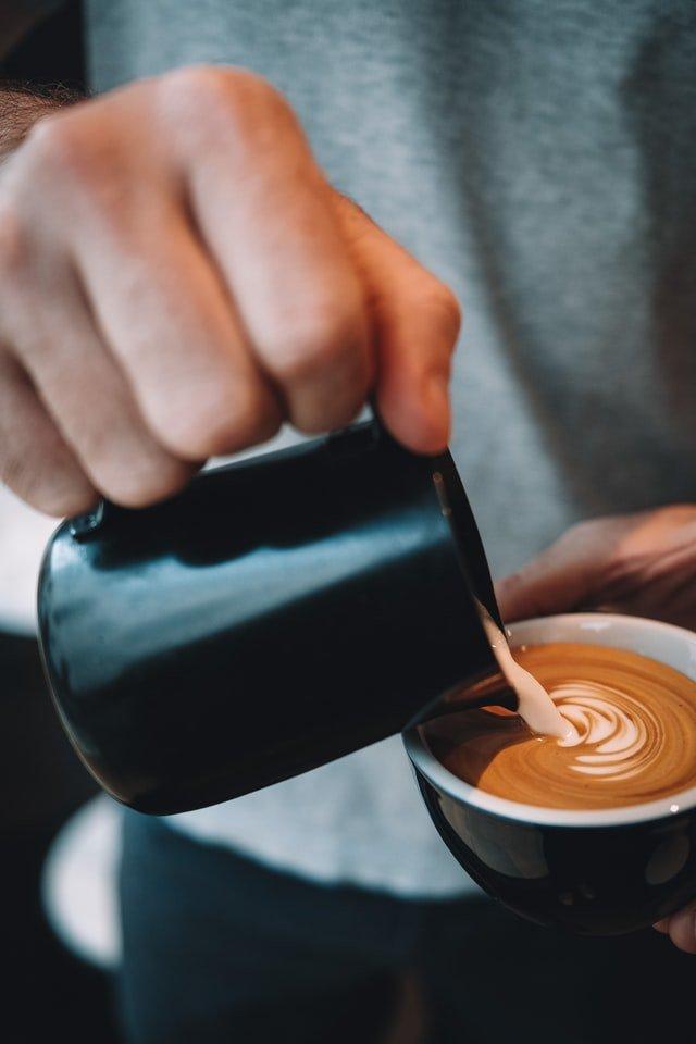 person pouring coffee milk