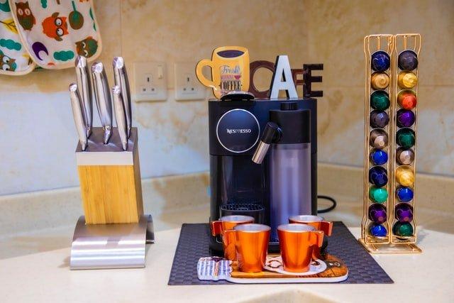 Nespresso coffee maker with pods and mugs