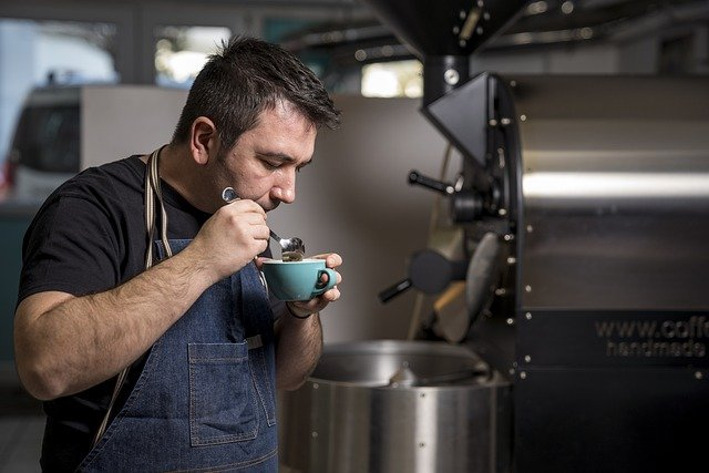 man smelling cup of coffee